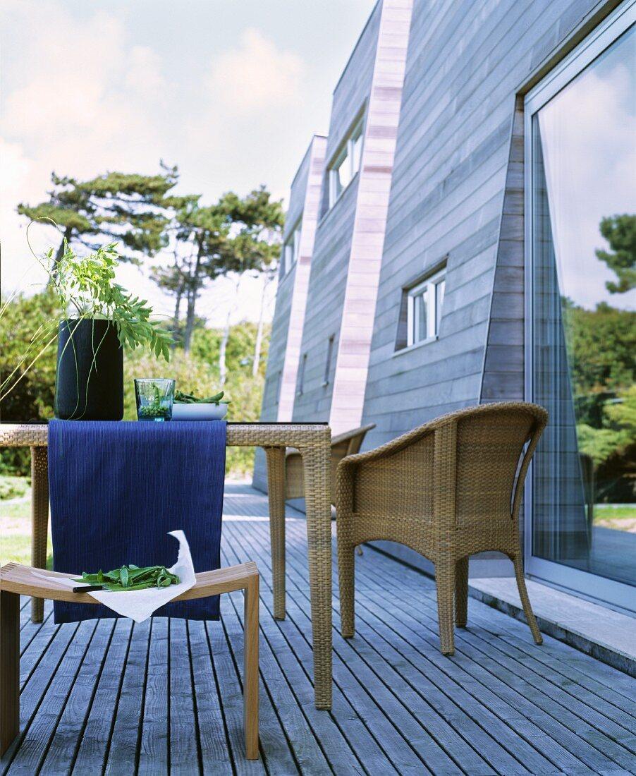 Wicker furniture on wooden terrace adjoining wooden façade