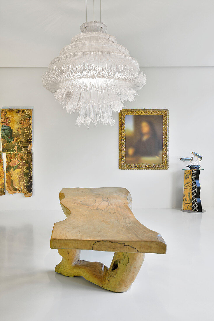 Rustic wooden table and modern artworks in white interior