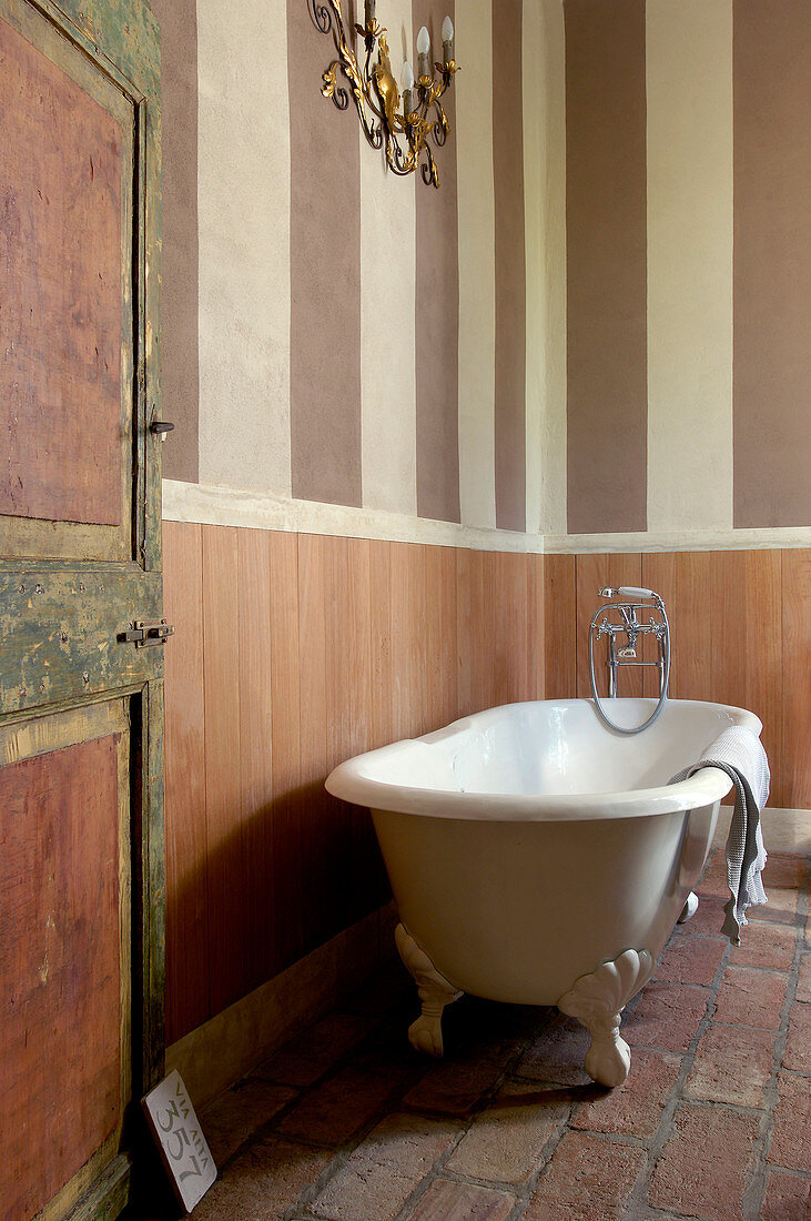 Free-standing bathtub next to striped wall with wainscoting