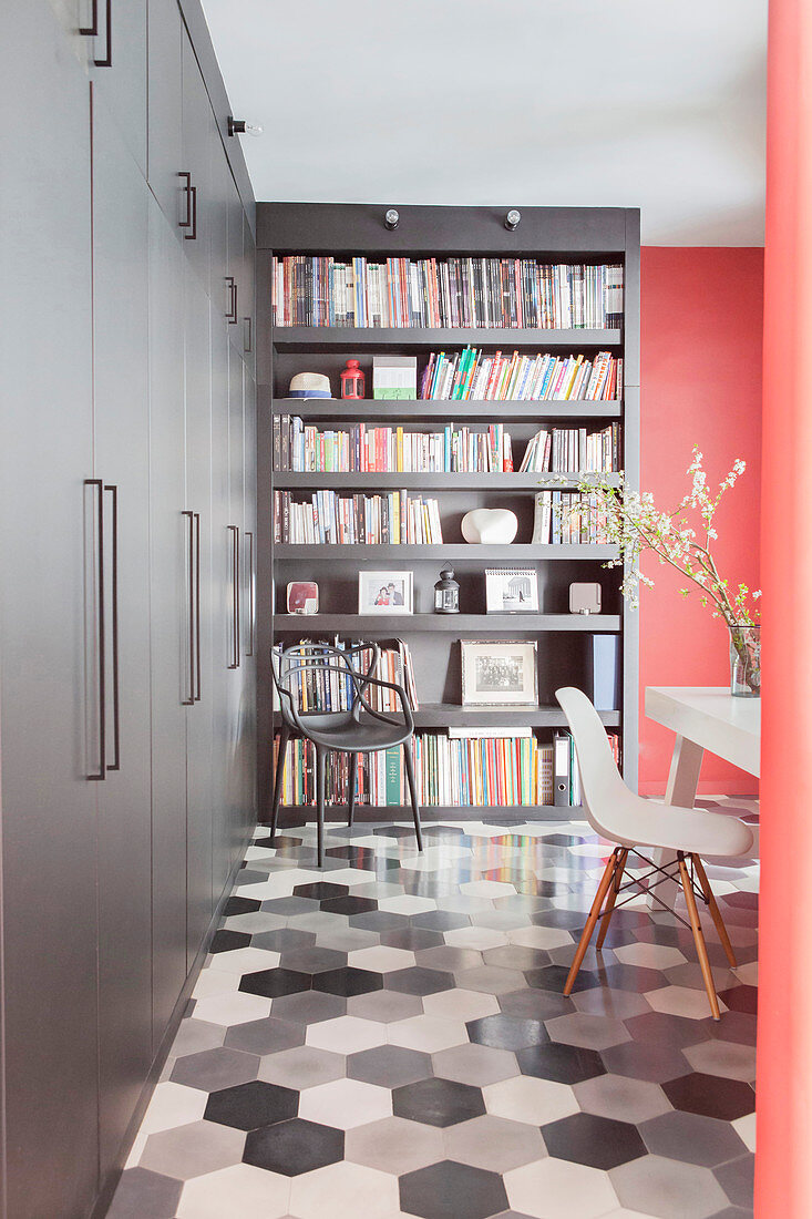 Grey fitted cupboards in study with honeycomb tiled floor