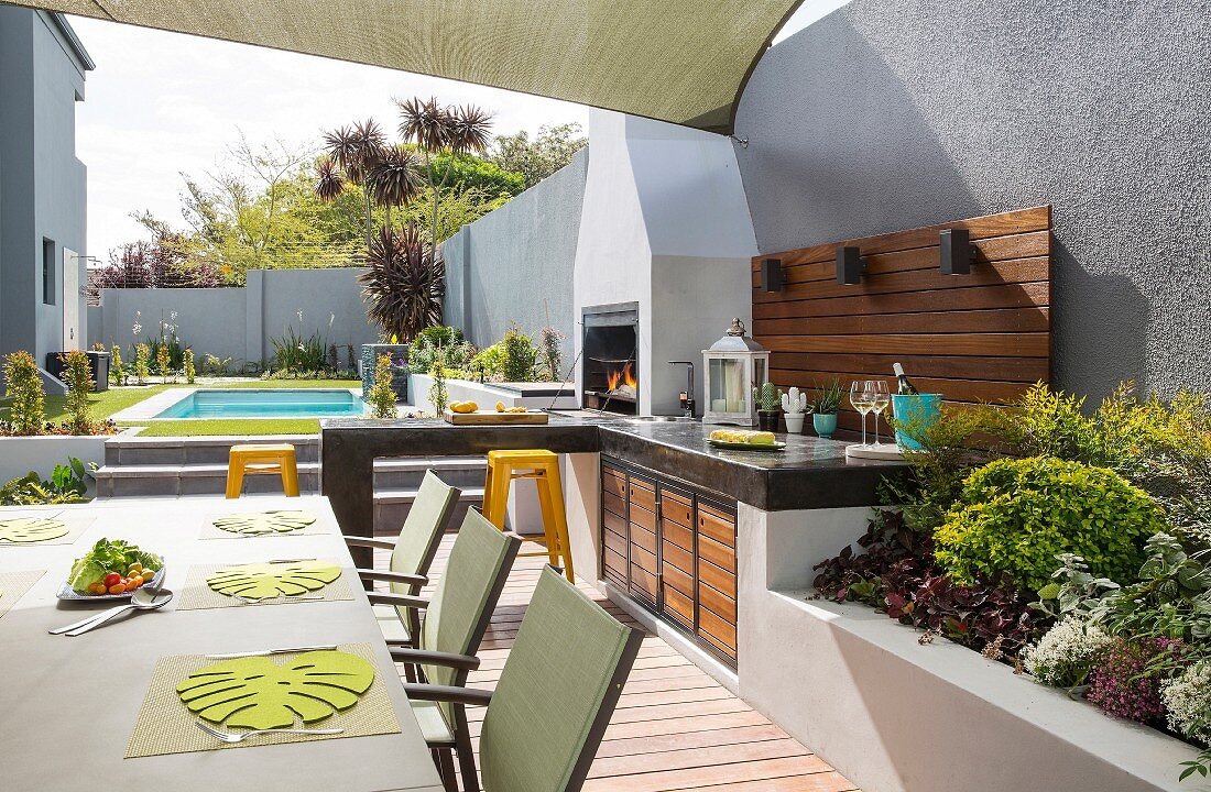 Pool, terrace and outdoor kitchen in summer garden surrounded by wall