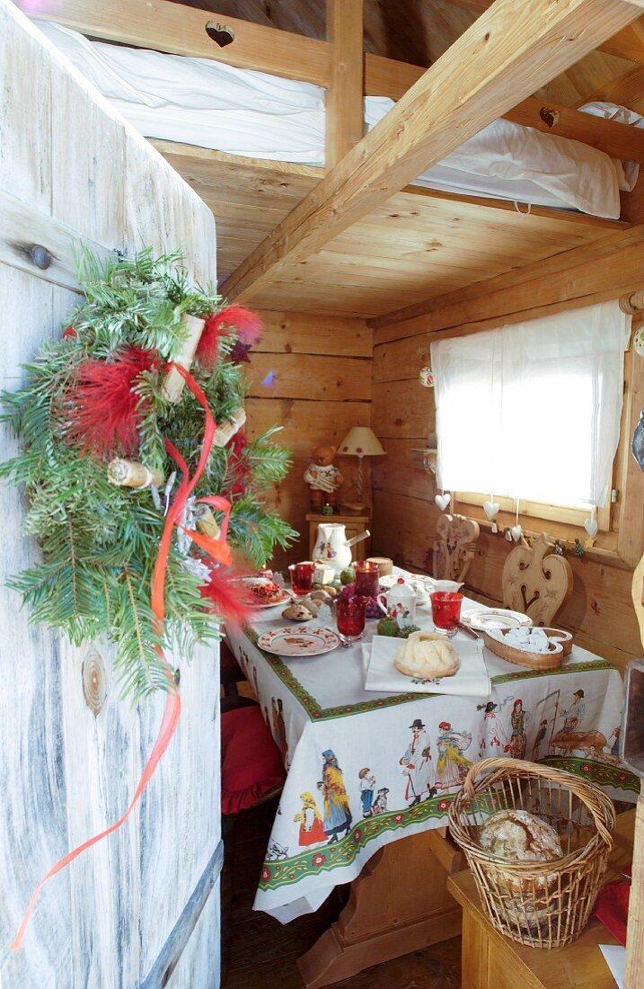 Blick durch offene Tür mit Kranz in Holzhütte mit gedecktem Tisch