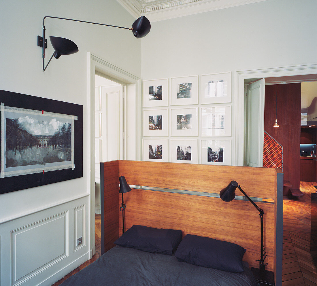 Double bed with reading lamps and wooden headboard in open-plan bedroom