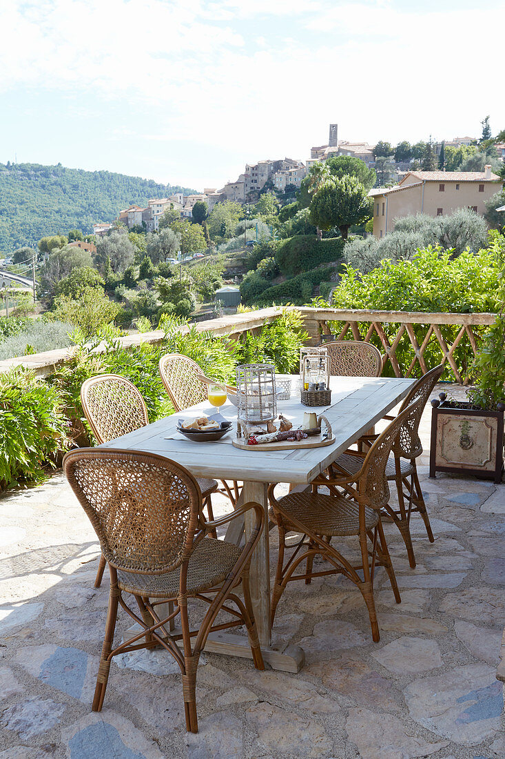 Wooden table and armchairs on roof terrace with stone floor