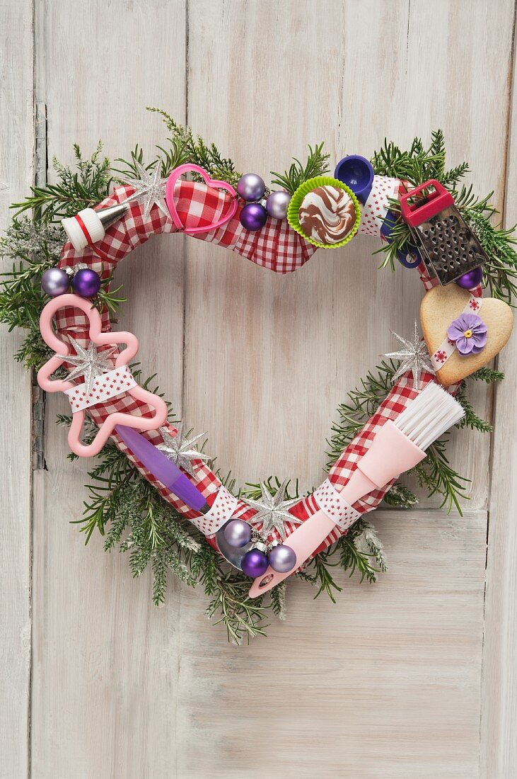 Heart-shaped Christmas door wreath decorated with baubles, baking utensils and biscuits