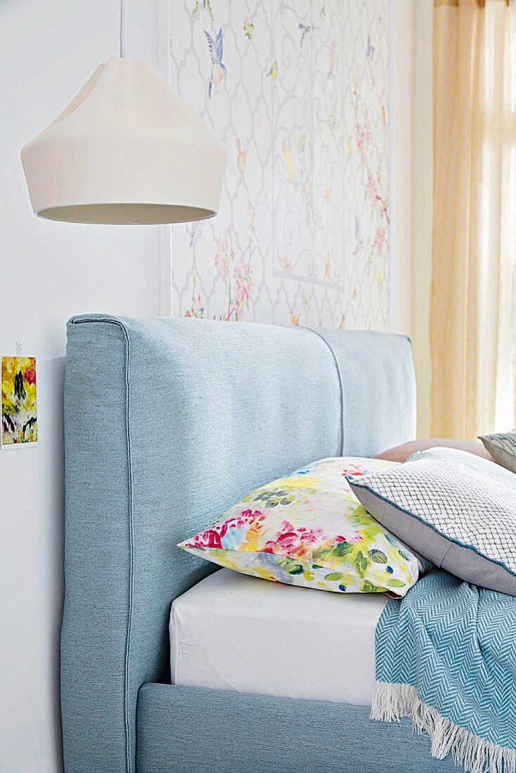 A light blue double bed with padded headboard (detail)
