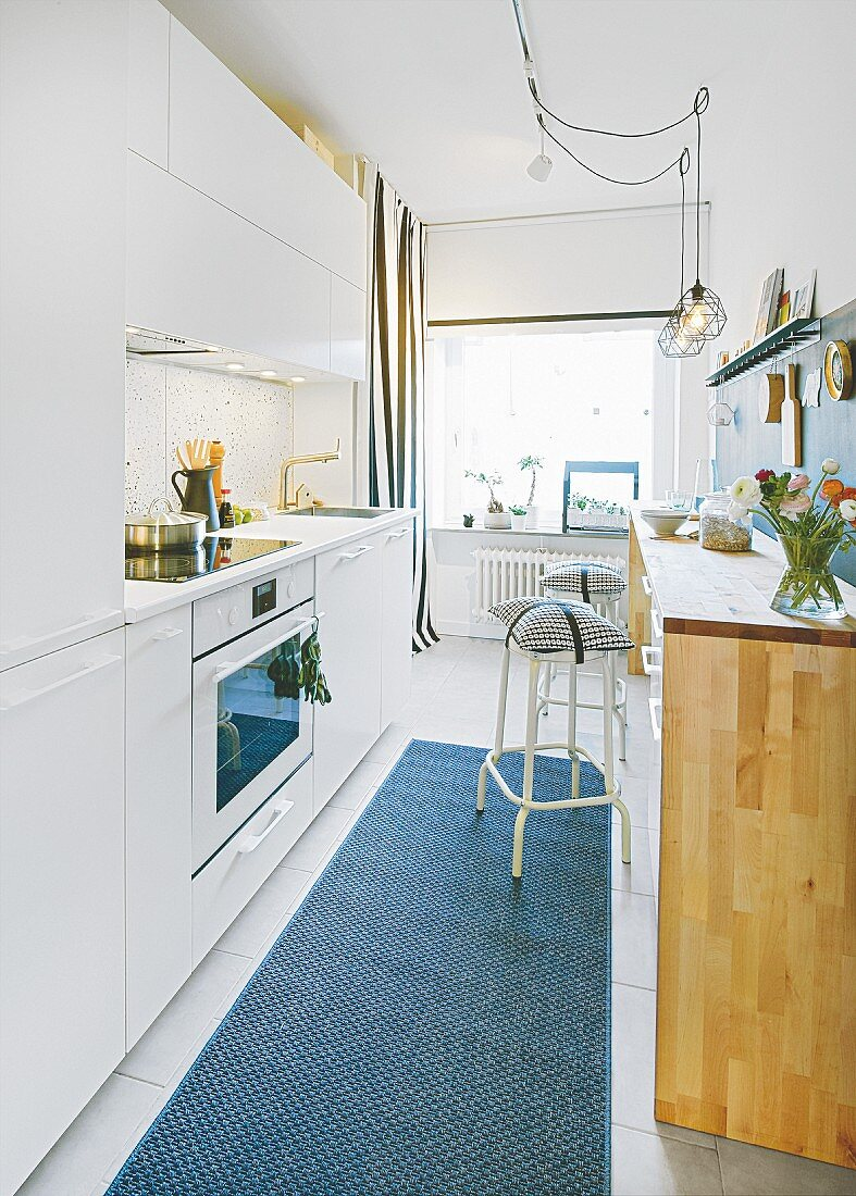 A compact kitchen with white fitted cupboards and a wooden breakfast bar