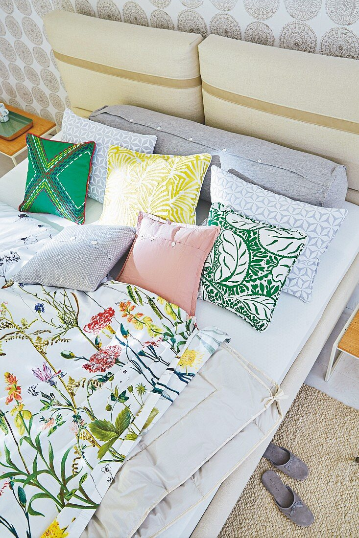 A double bed with floral bed linen and cushions