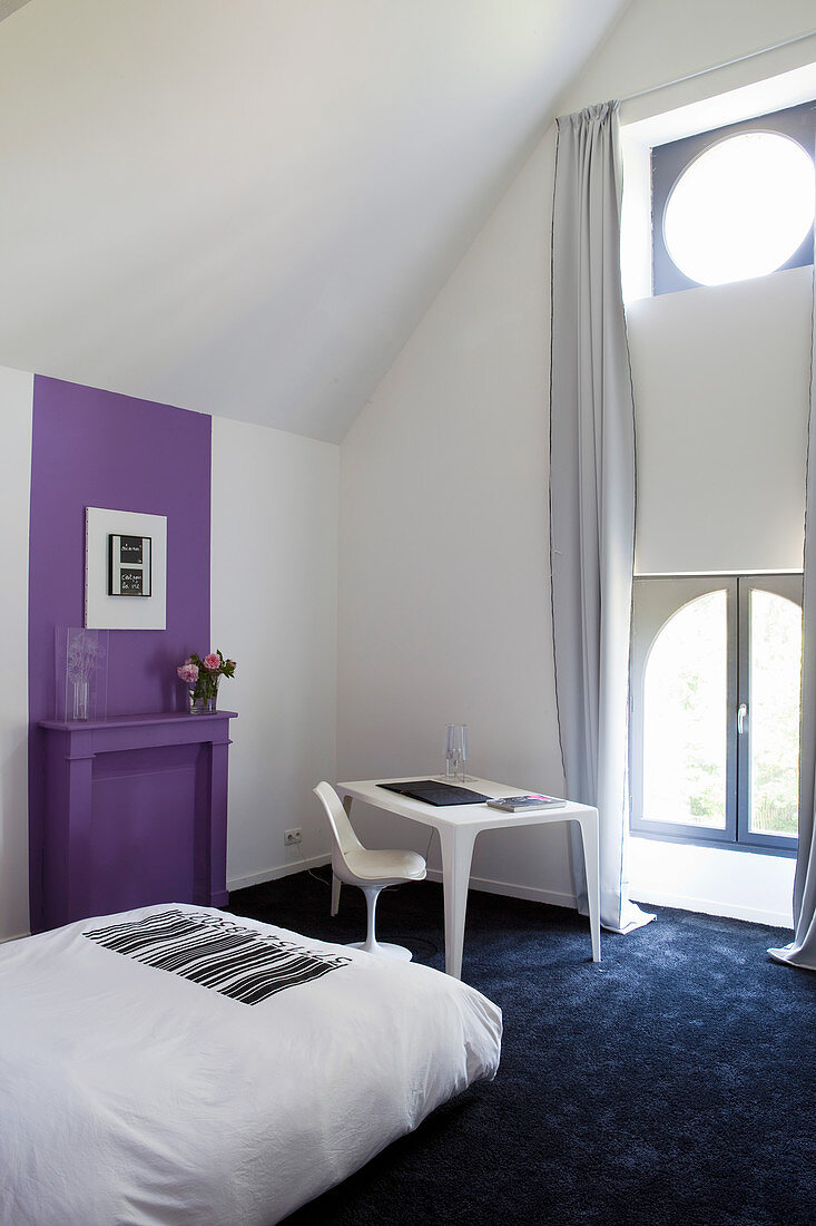 Artistic bedroom with purple accent on wall