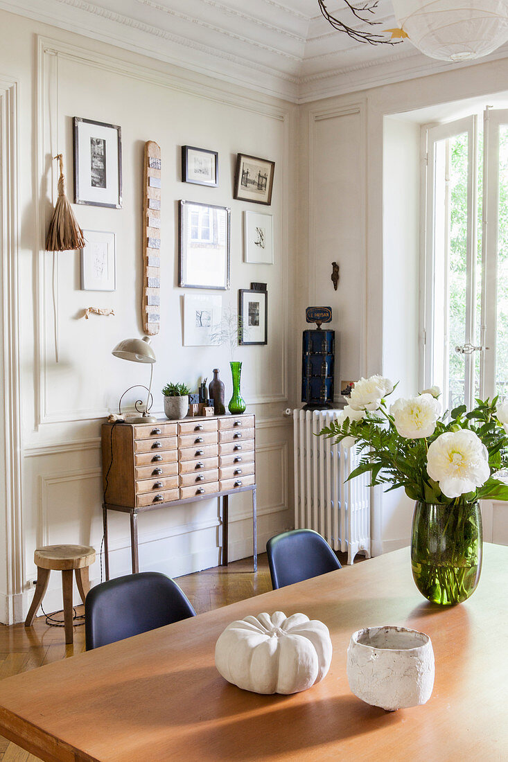 View past flowers on dining table to chest of drawers below gallery of pictures on wall