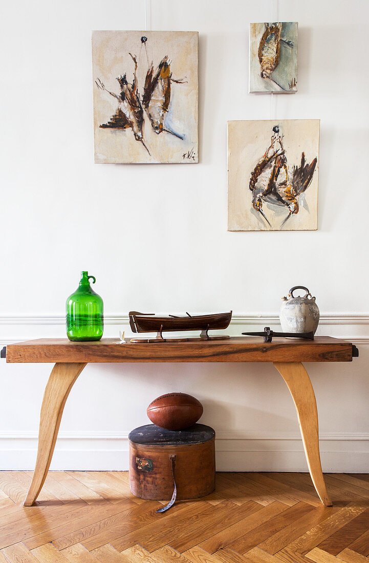 Pictures of shot birds above wooden console table