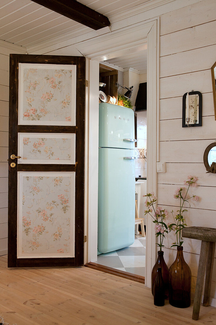 Panelled door with floral wallpaper leading into kitchen