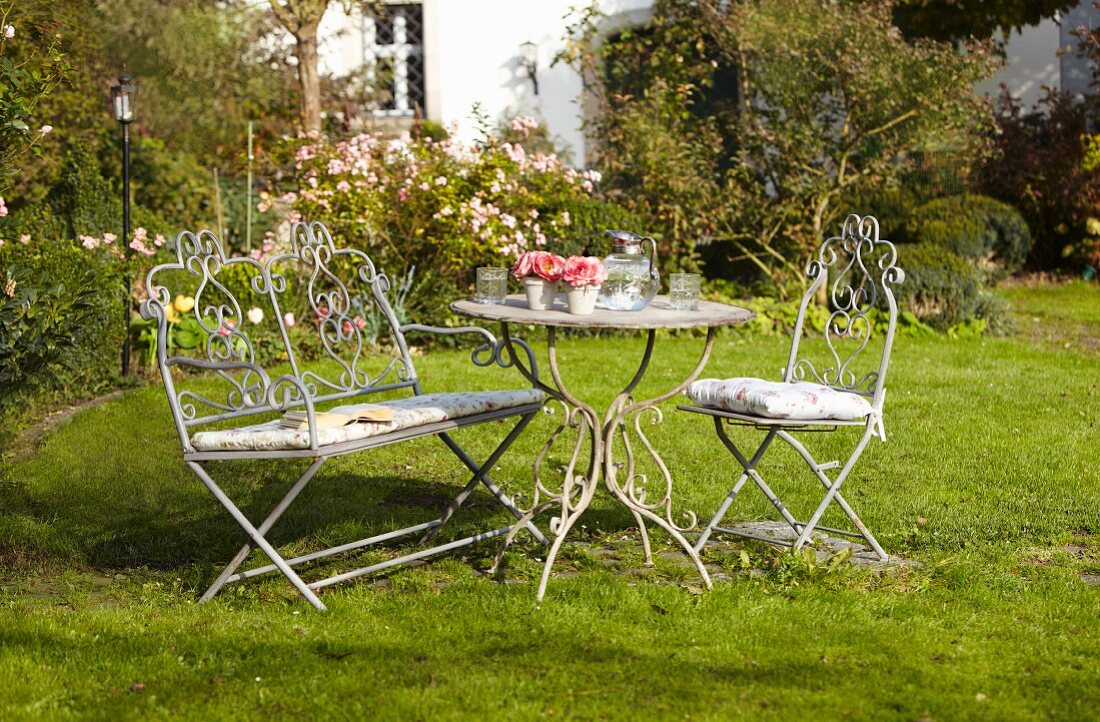 Romantic seating area with vintage garden furniture on lush lawn