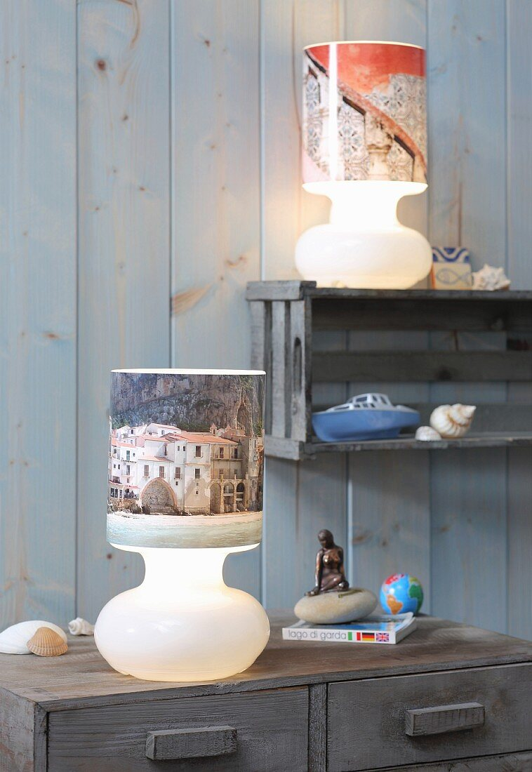 Table lamps with lampshades covered in holiday photos against board wall