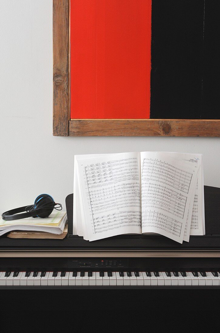 E-Piano mit Notenblättern und Kopfhörer vor rot-schwarzem, modernem Bild