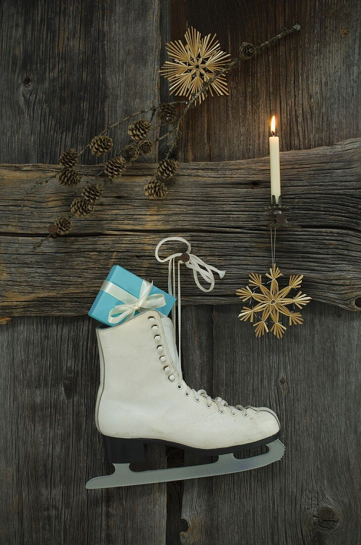Christmas decoration and ice skate with present hung on wooden wall