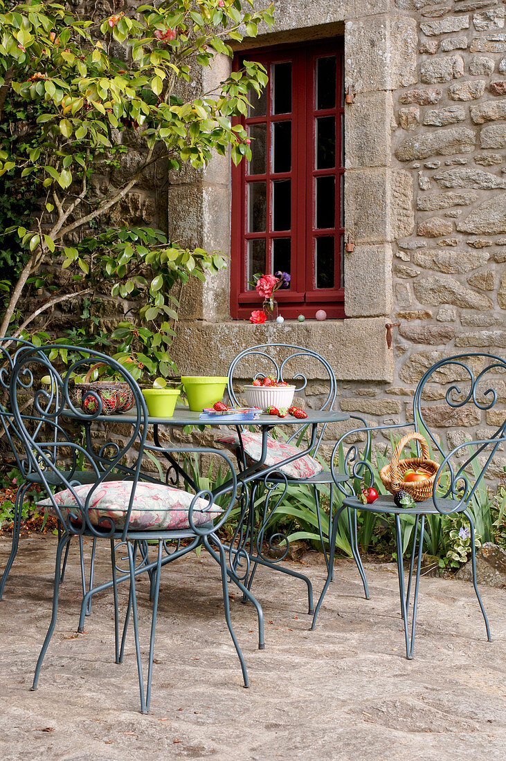 Ornate metal chairs and table outside window of stone house