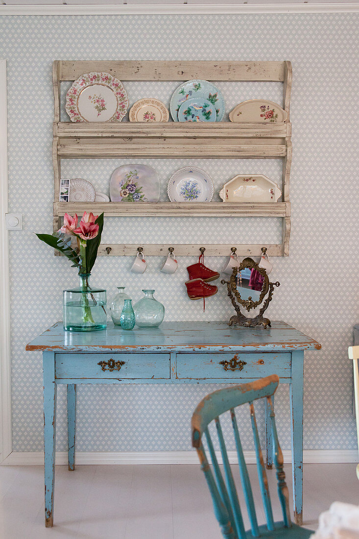 Vintage-style plates on plate rack above pale blue table