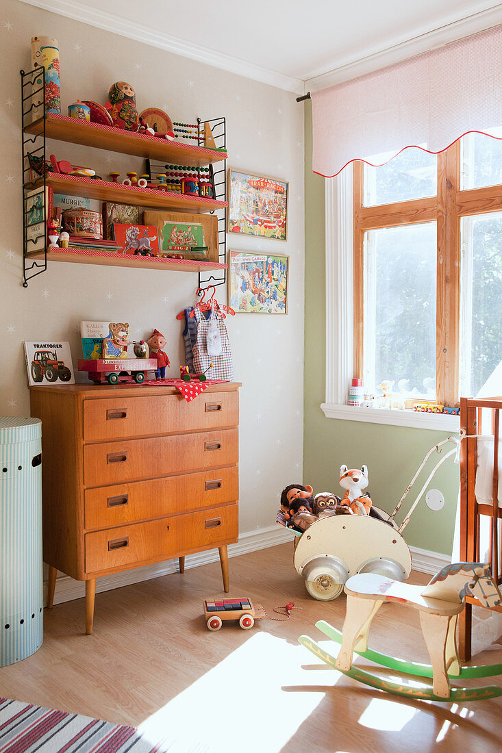 Shelves above wooden chest of drawers in vintage-style nursery