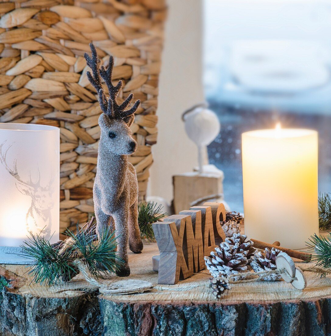 Rustic Christmas arrangement of reindeer figurine, candle, lantern and pine cones on slice of tree trunk