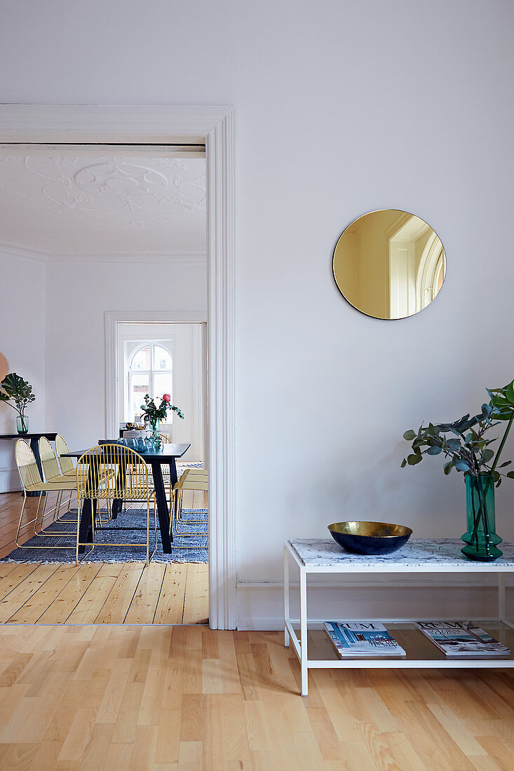 Side table below round mirror on wall and view into dining room