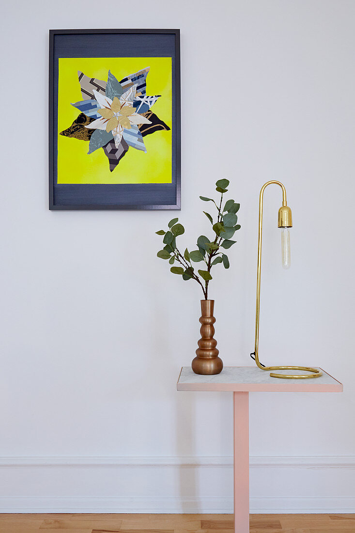 Vase of leaves and reading lamp on side table below colourful artwork