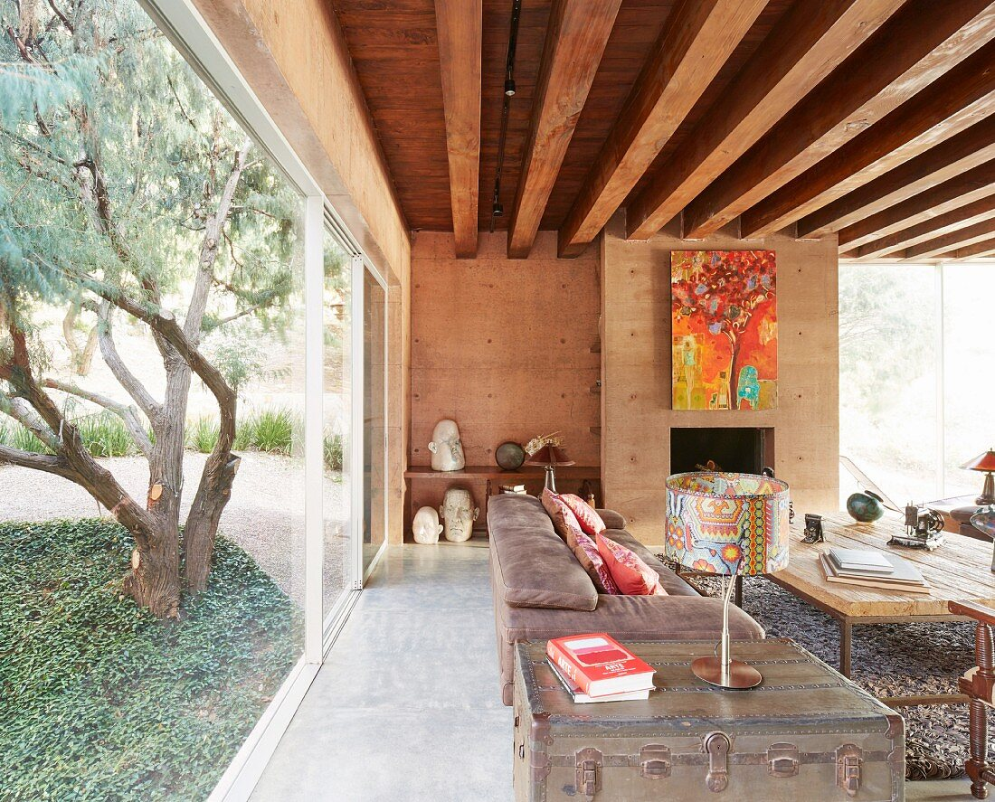 Ethnic-style living room with glass wall looking out over garden