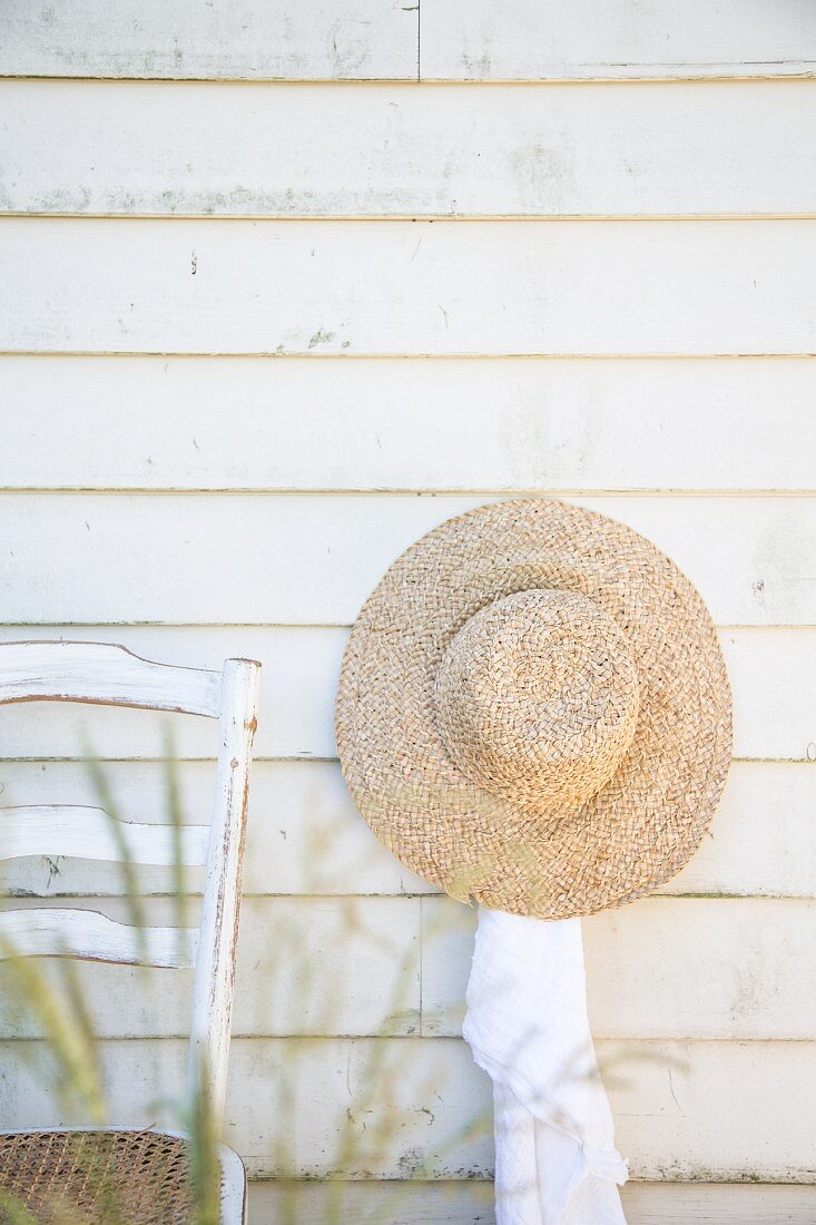 Straw hat hung on clapboard wall next to chair