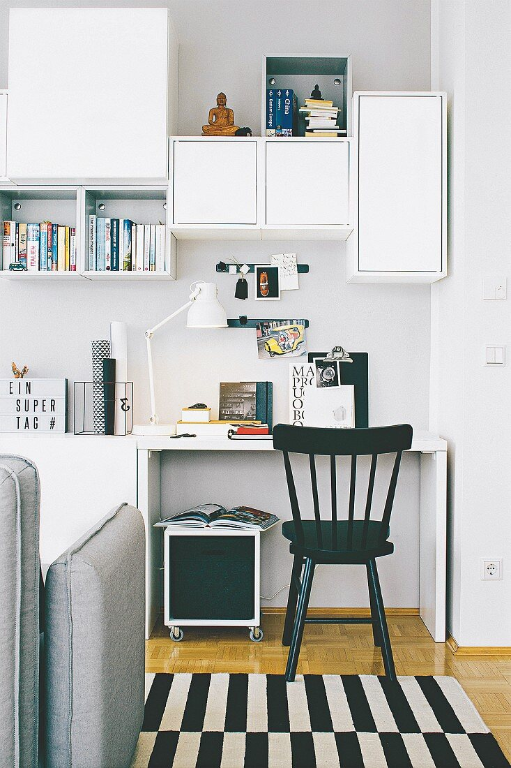 A workspace with open and closed shelves in a living room