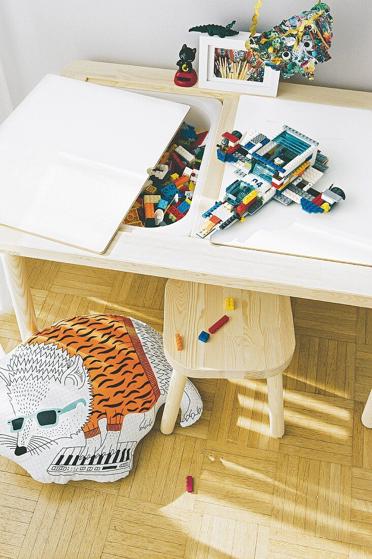 A child's play table with detachable panels and storage