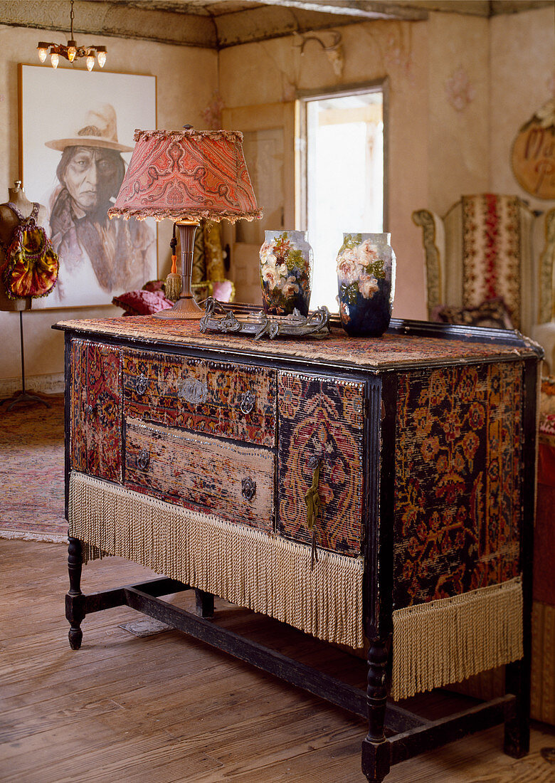 Cabinet covered with pieces of old rug and fringes