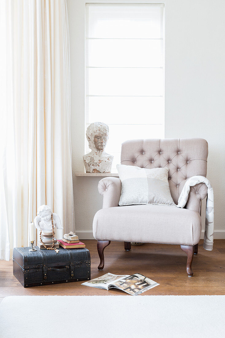 Old trunk used as side table next to beige armchair