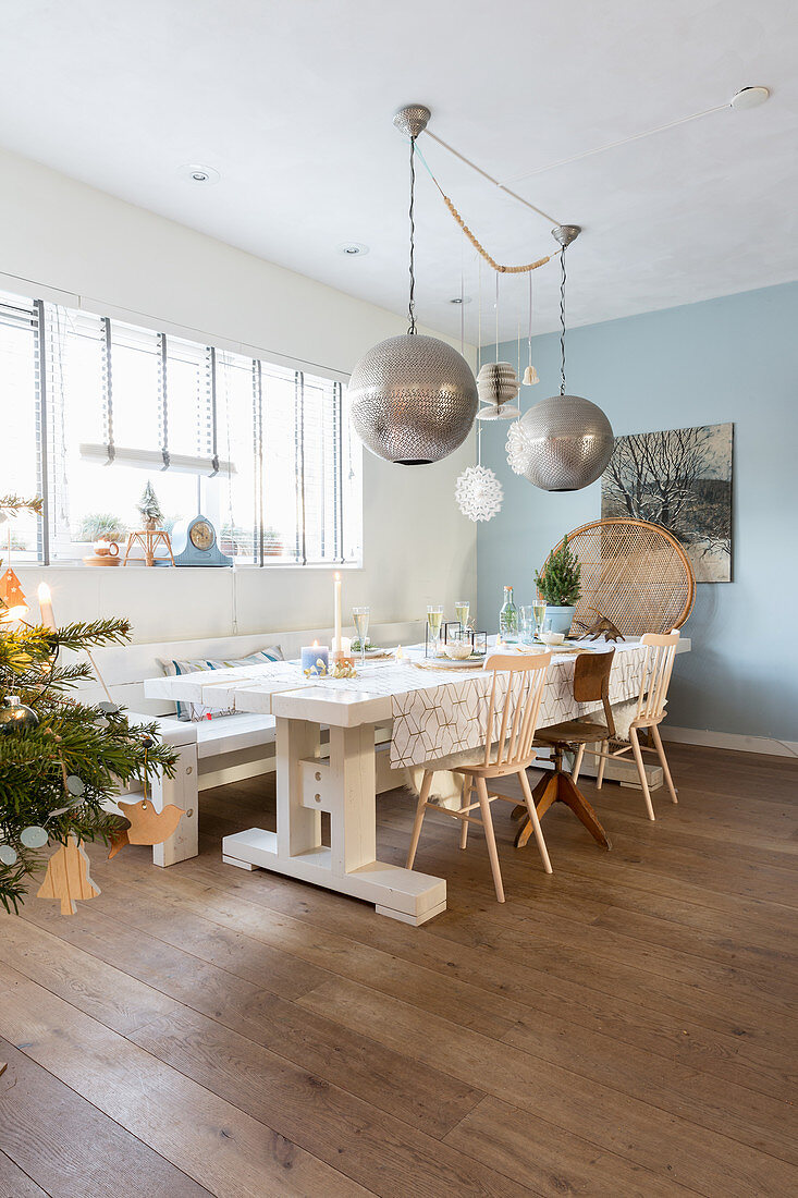 Large spherical lamps above dining table and various chairs