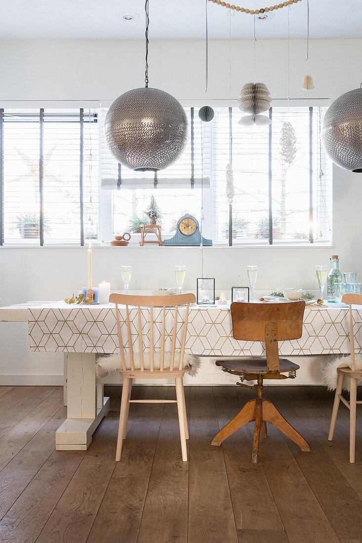 Spherical silver lamps above dining table and various chairs