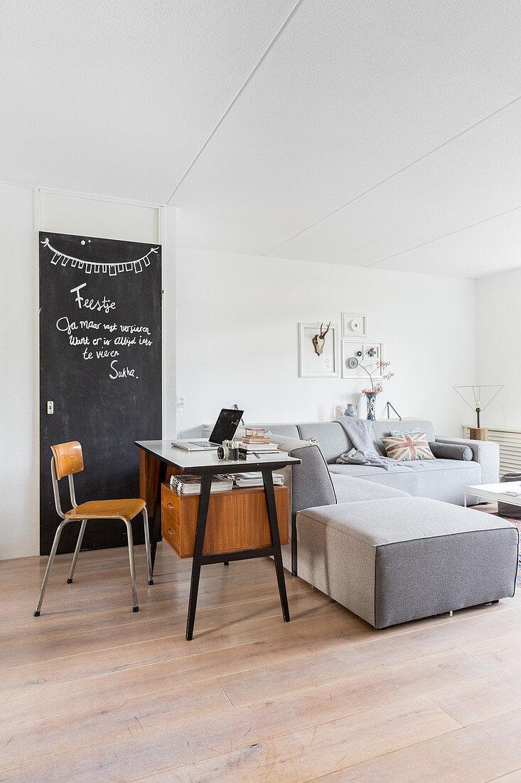 Retro desk and chalkboard behind modern grey sofa
