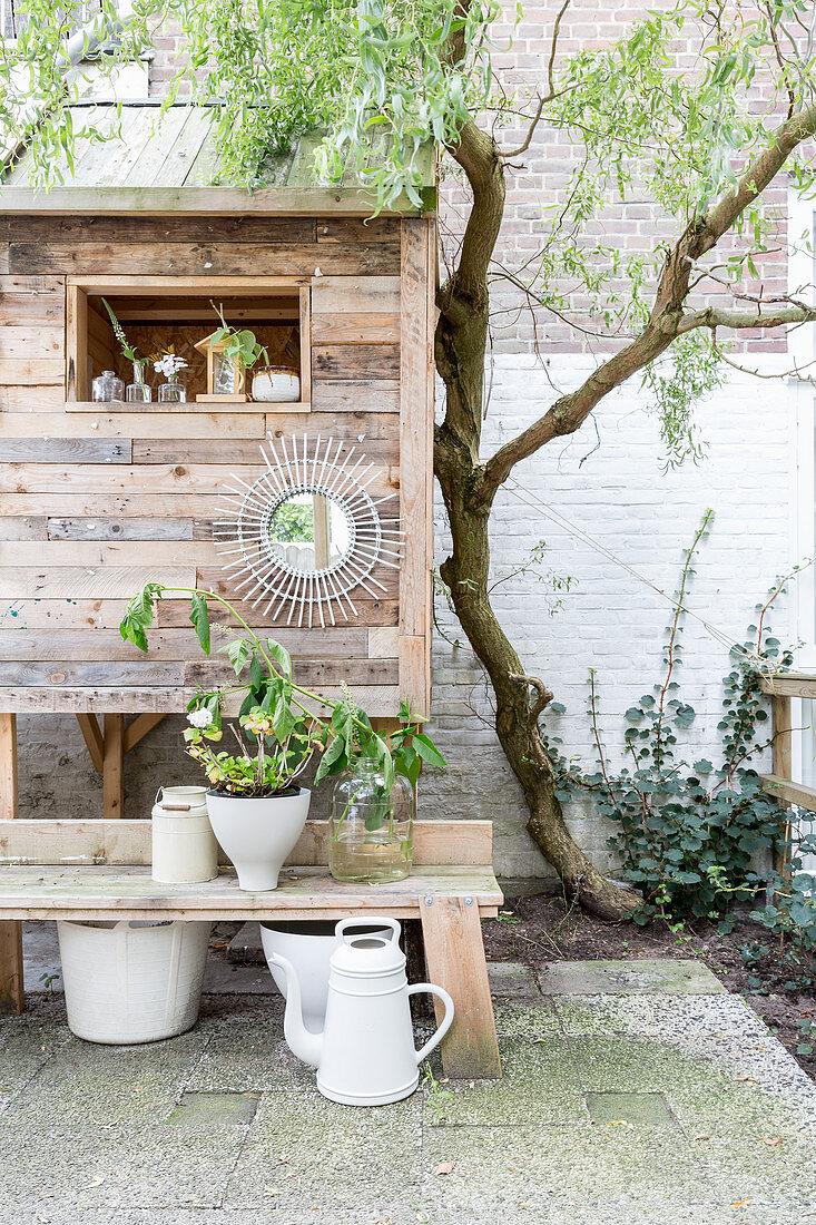 Plants on wooden bench in front of playhouse in courtyard garden