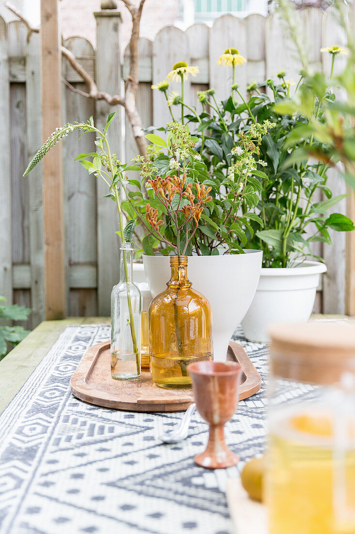 Flowers and vases in shades of yellow and brown on table in garden