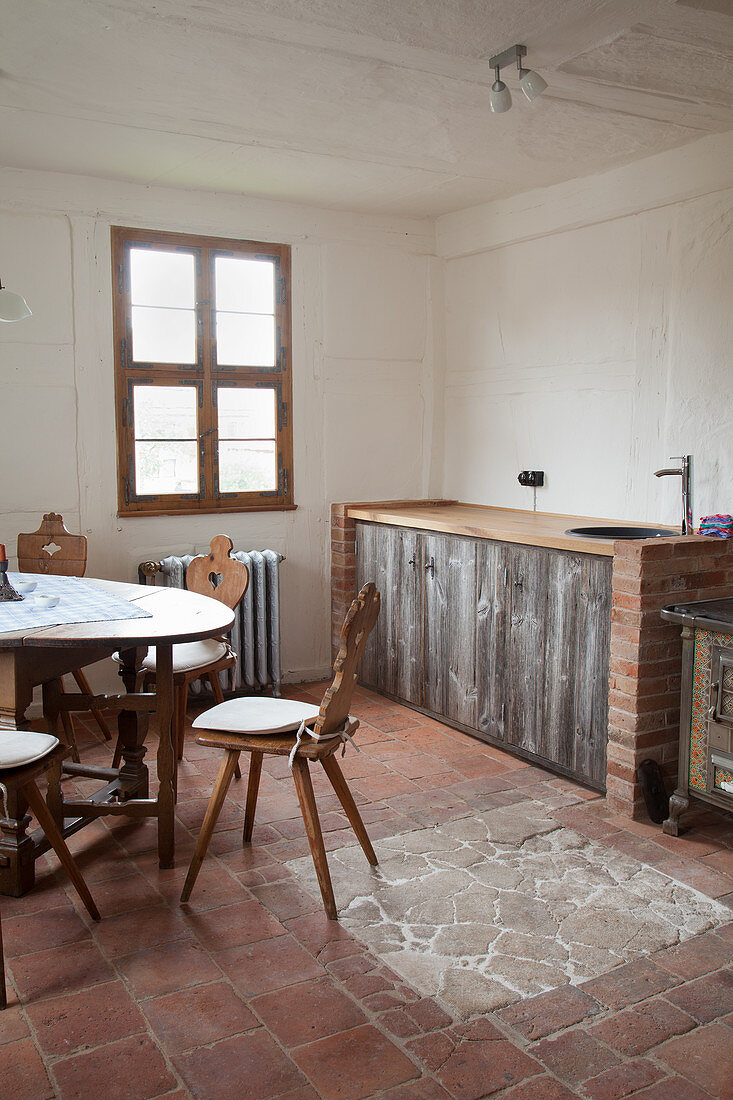 Farmhouse chairs around table in kitchen with terracotta floor tiles