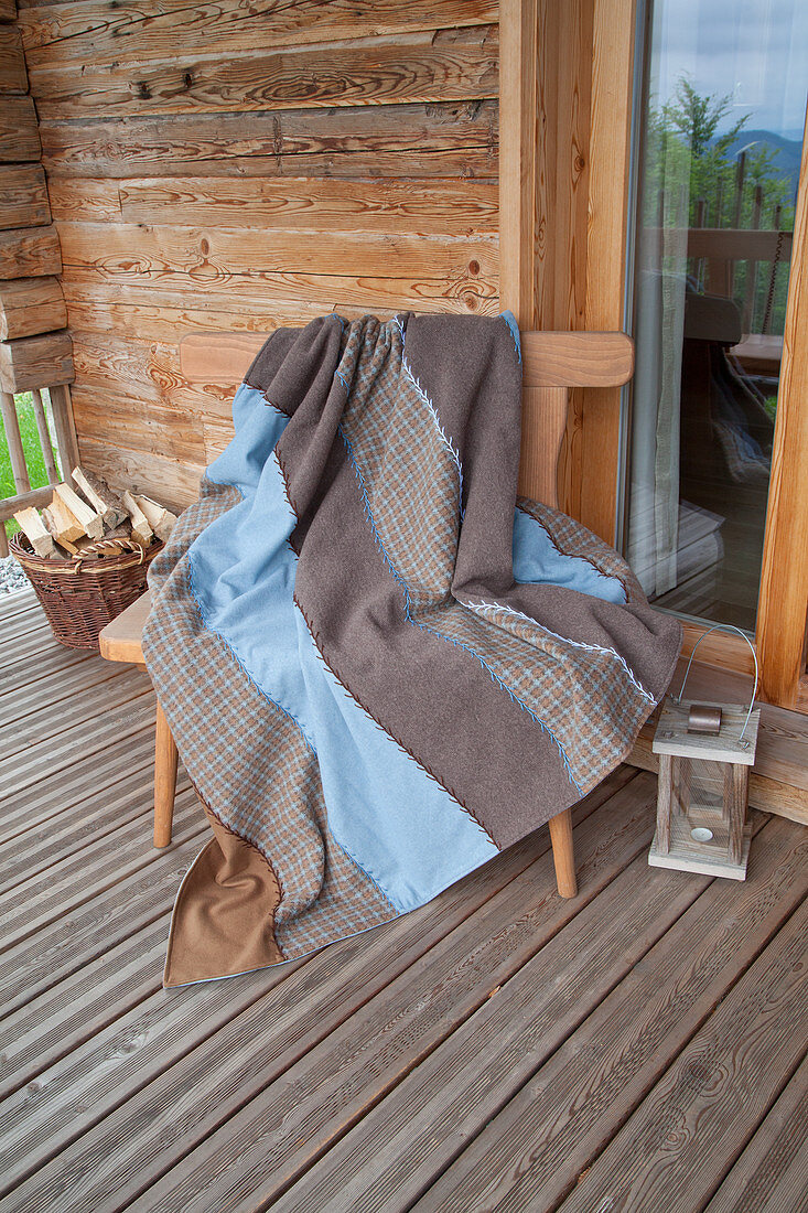 Brown and blue blanket made from strips of various fabrics