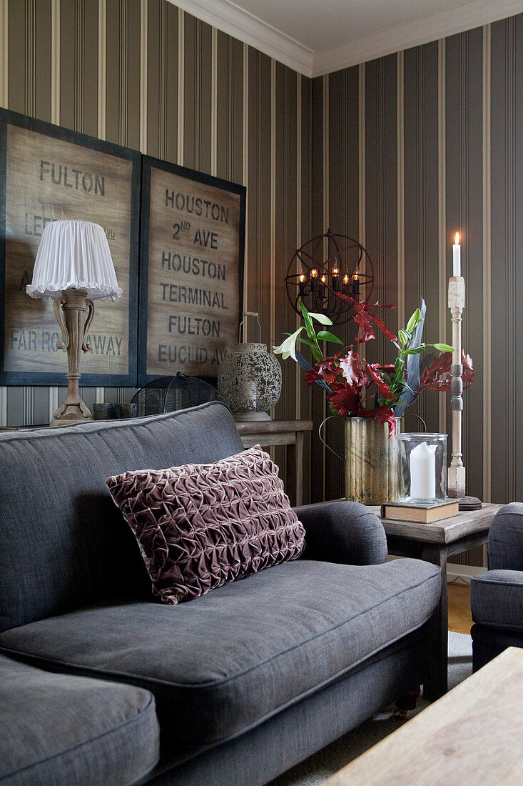 Velvet scatter cushion n grey sofa in cosy living room with striped wallpaper