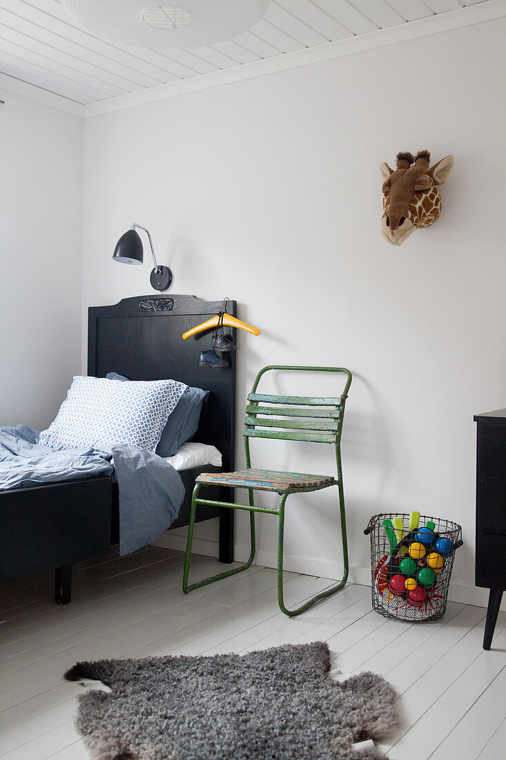 Old green chair next to black bed in child's bedroom