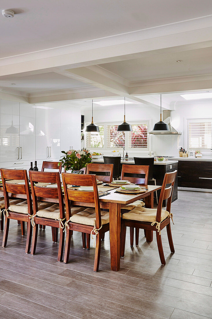 Dining area with wooden table and chairs, in the background open kitchen with porcelain floor tiles in a wood look