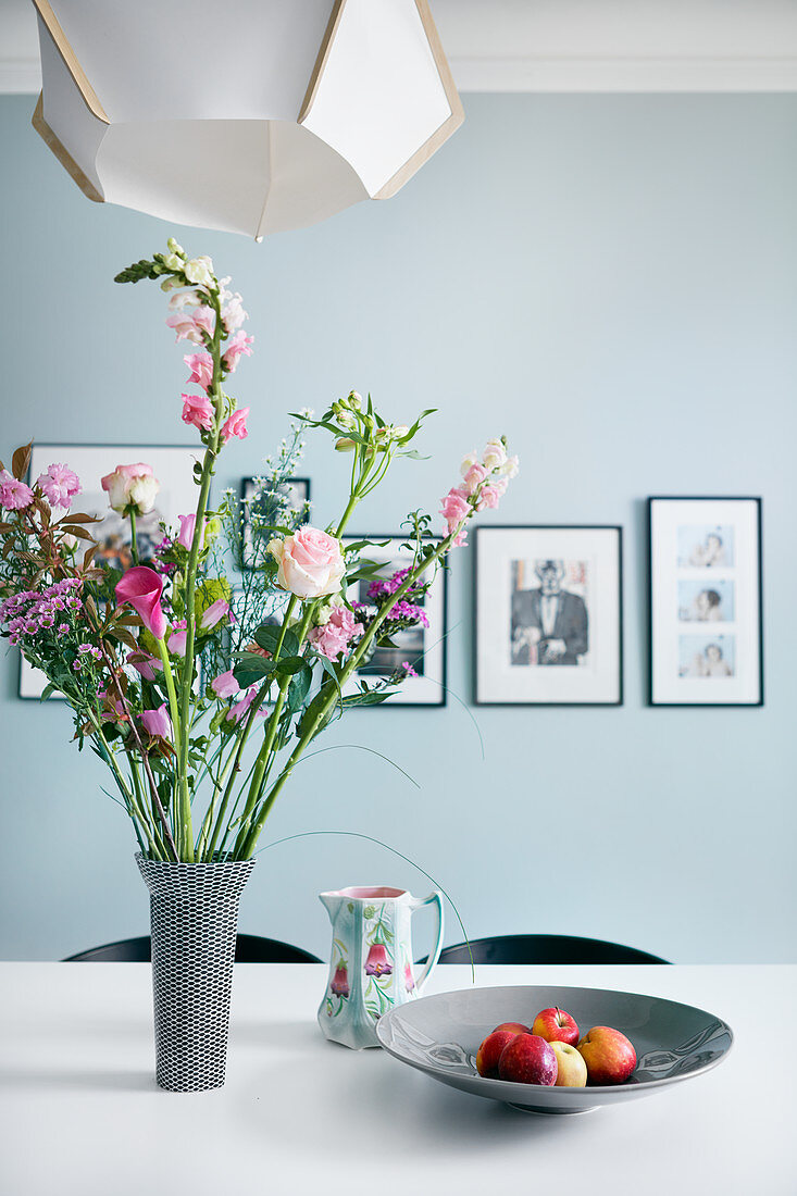 Bouquet in shades of pink on dining table in front of pale blue wall