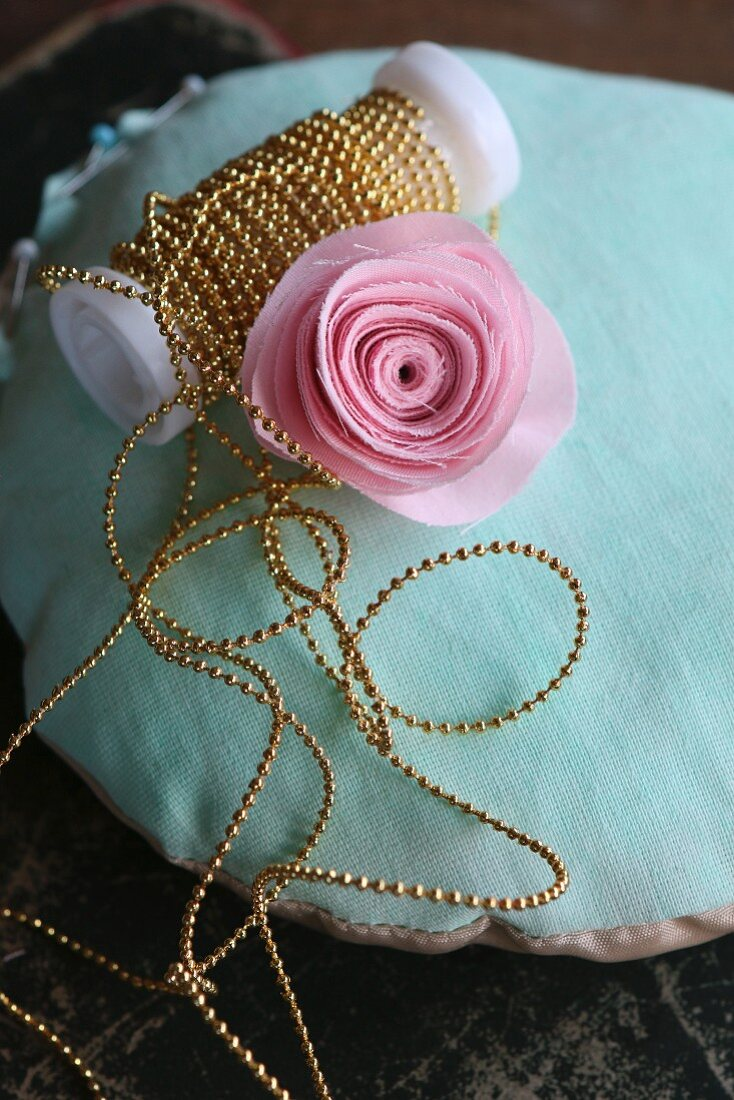 Fabric rose and string of beads on turquoise pincushion