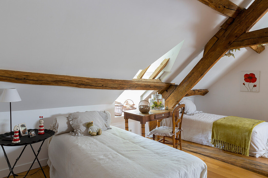 Twin beds in attic bedroom with rustic wooden beams
