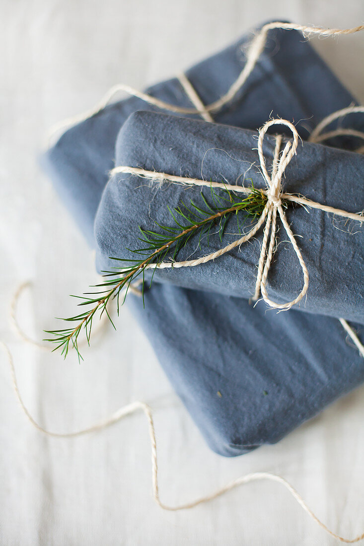 Gifts wrapped in blue fabric tied with parcel string
