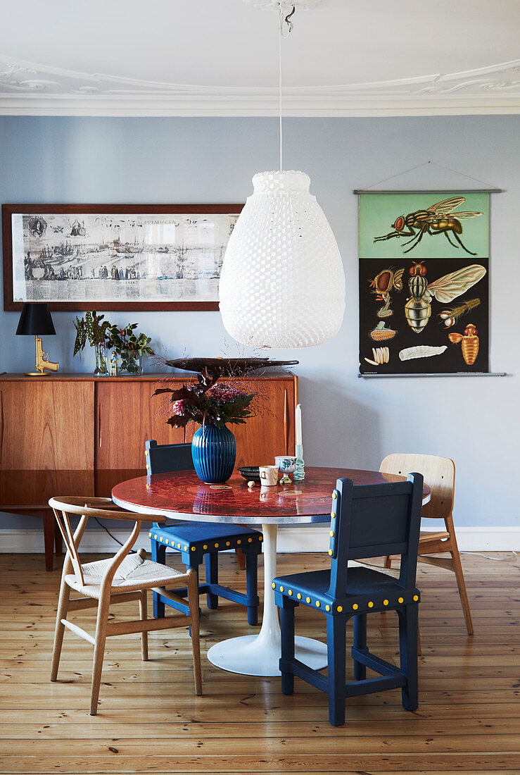 Various chairs at round table in front of pale blue wall
