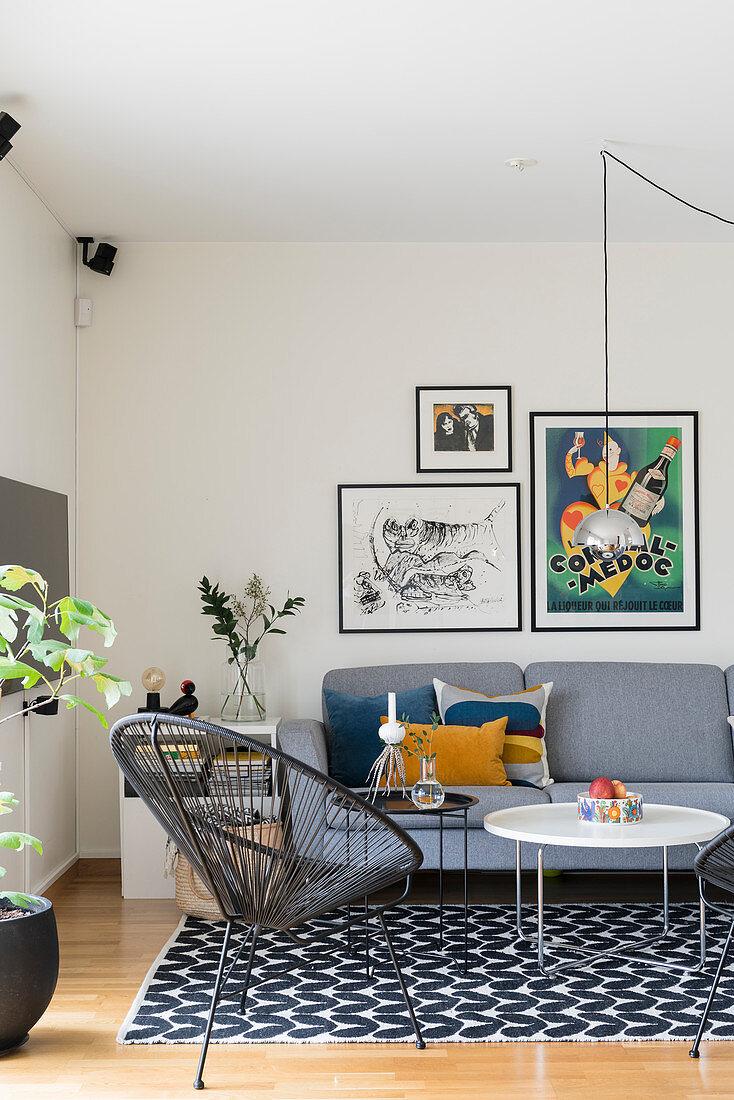 Klassikerstuhl, Coffeetable und graues Polstersofa im Wohnzimmer