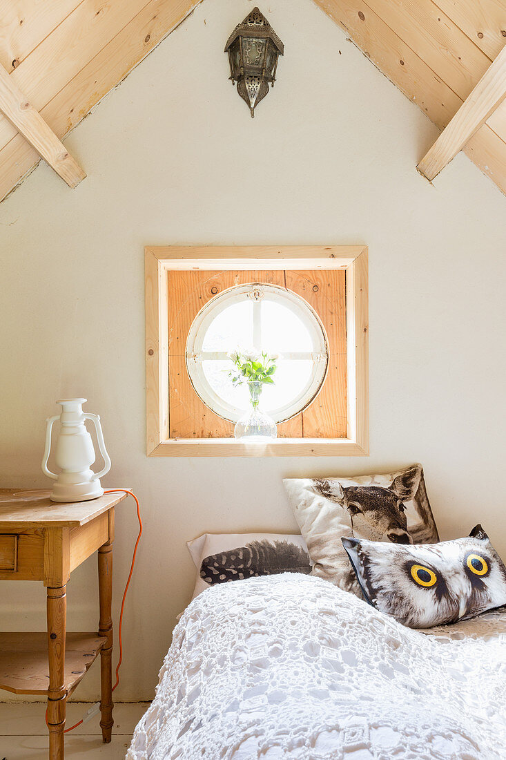 Cushions with animal motifs on bed below round window in gable end wall