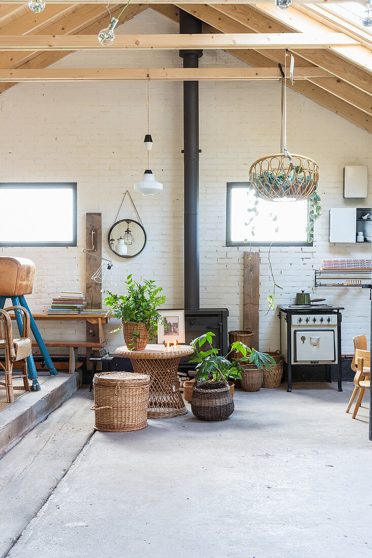 High-ceilinged room with concrete floor, brick wall and vintage furniture